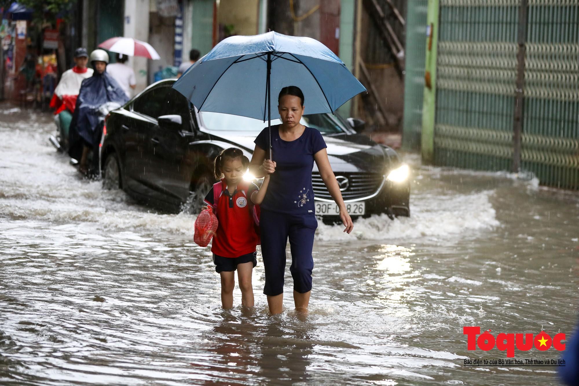 Hình ảnh xưa nay hiếm ở Thủ đô Hà Nội  cha mẹ cõng con vượt sông trong phố đến trường1