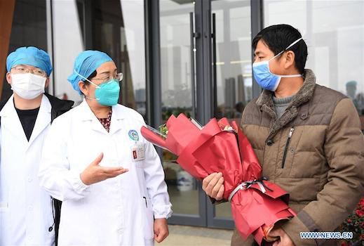 Bác sĩ chữa trị tặng hoa cho bệnh nhân. Ảnh: News.cn
