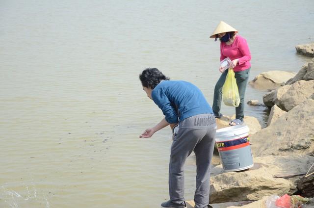 Hà Nội: Người dân đổ xô thả cá chép tiễn ông Táo về trời, rác tràn trên bến sông   - Ảnh 4.