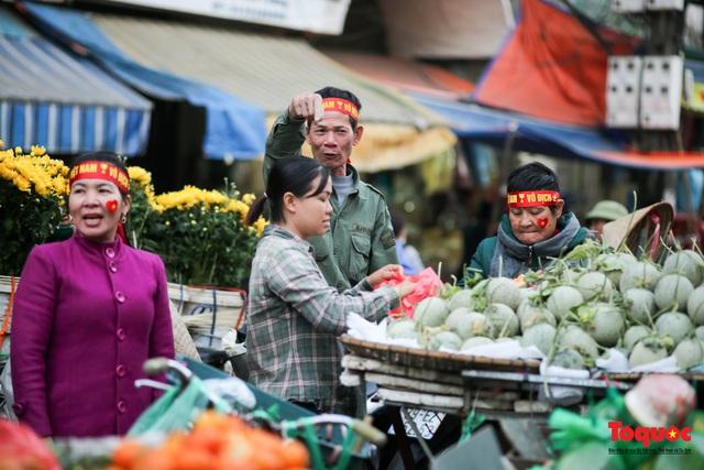 """Tiểu thương chợ Cầu Đông vừa bán hàng vừa tranh thủ """"lên đồ"""" cổ vũ U22 Việt Nam - Ảnh 5."""