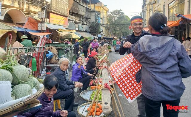 """Tiểu thương chợ Cầu Đông vừa bán hàng vừa tranh thủ """"lên đồ"""" cổ vũ U22 Việt Nam - Ảnh 2."""