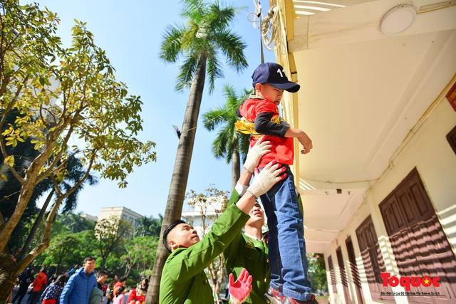 Các em nhỏ học kỹ năng đu dây thoát hiểm khi có sự cố cháy từ nhà cao tầng - Ảnh 9.
