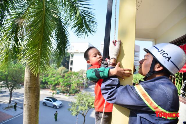 Các em nhỏ học kỹ năng đu dây thoát hiểm khi có sự cố cháy từ nhà cao tầng - Ảnh 4.