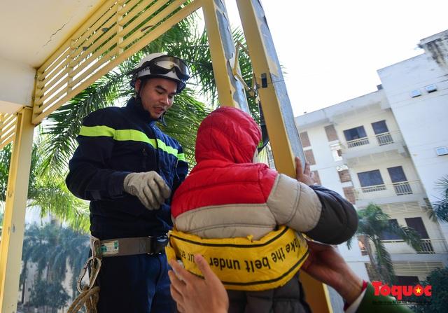 Các em nhỏ học kỹ năng đu dây thoát hiểm khi có sự cố cháy từ nhà cao tầng - Ảnh 3.