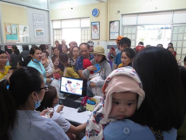 Nhiều người dậy từ 3 giờ sáng đăng ký lấy số thứ tự để được tiêm vắc xin 6 trong 1 cho con - Ảnh 2.