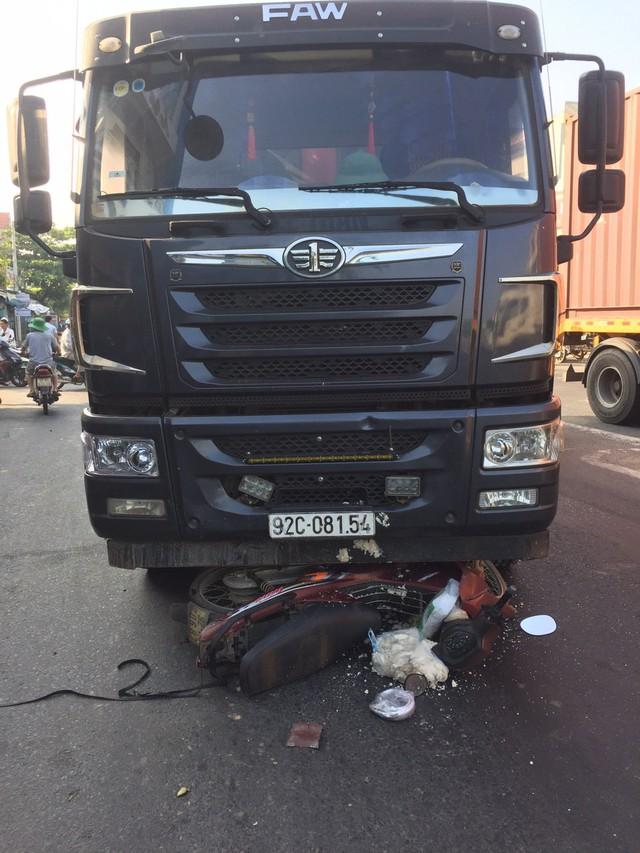 Xe máy bị cuốn vào gầm xe tải, một phụ nữ bị thương nặng - Ảnh 1.