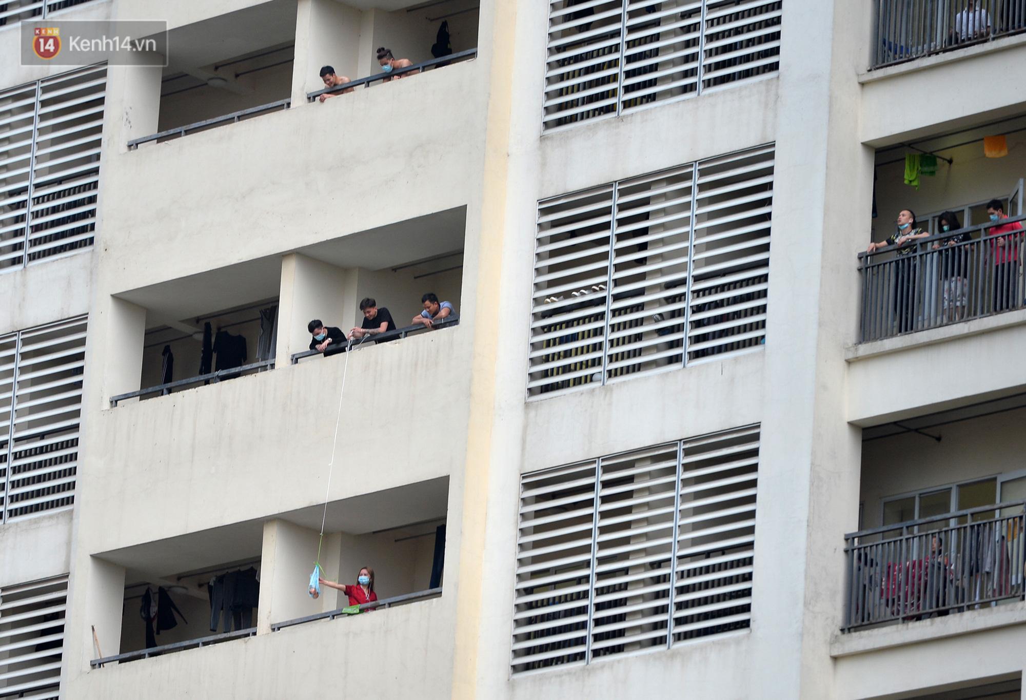 Mẹ bắn tim từ xa cho con gái, các anh thanh niên tầng trên cột dây thả túi hoa quả cho chị em tầng dưới trong khu cách ly ở Hà Nội - Ảnh 9.