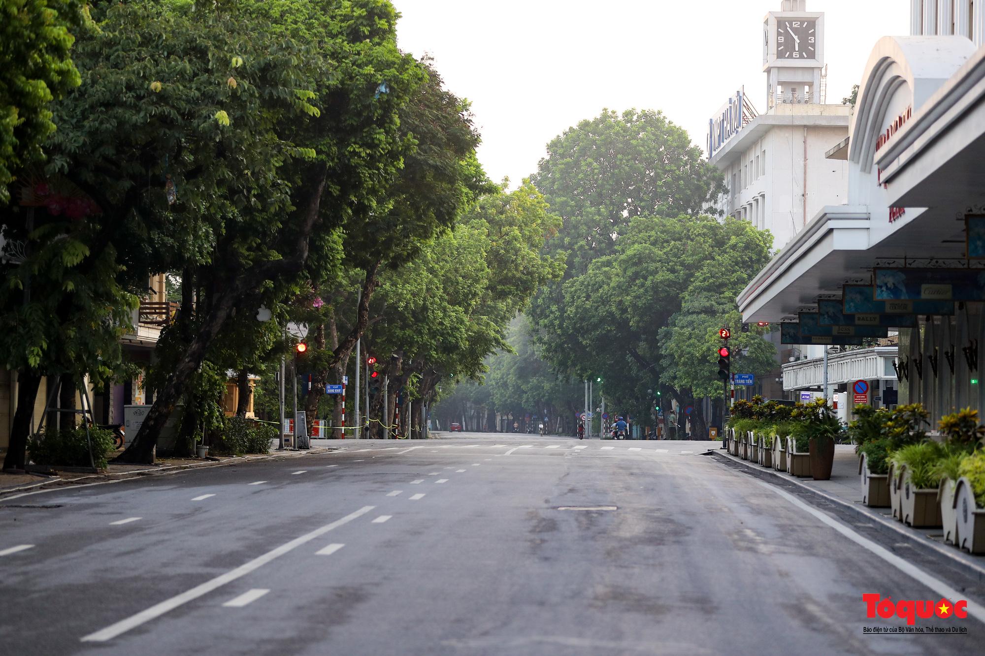 Đường phố Hà Nội vắng vẻ trong ngày đầu thực hiện giãn cách toàn xã hội - Ảnh 2.