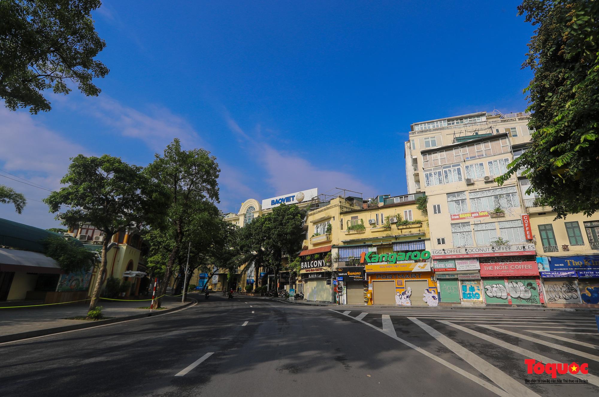 Đường phố Hà Nội vắng vẻ trong ngày đầu thực hiện giãn cách toàn xã hội - Ảnh 14.