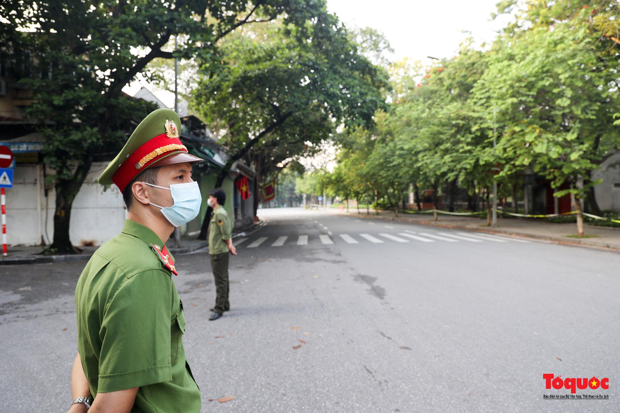 Đường phố Hà Nội vắng vẻ trong ngày đầu thực hiện giãn cách toàn xã hội - Ảnh 6.