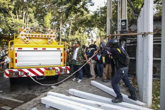 <br /> Người biểu tình giật đổ rào chắn của sân vận động sáng 26-12. Ảnh: REUTERS