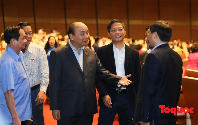 Thủ tướng trao đổi với các đại biểu bên lề hành lang nghị trường ngày đầu phiên chất vấn kỳ 8 Quốc hội khóa XIV - Ảnh 1.