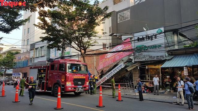 Cảnh sát giúp dân di chuyển cửa hàng hoa cạnh ngôi nhà bị sập - Ảnh 1.