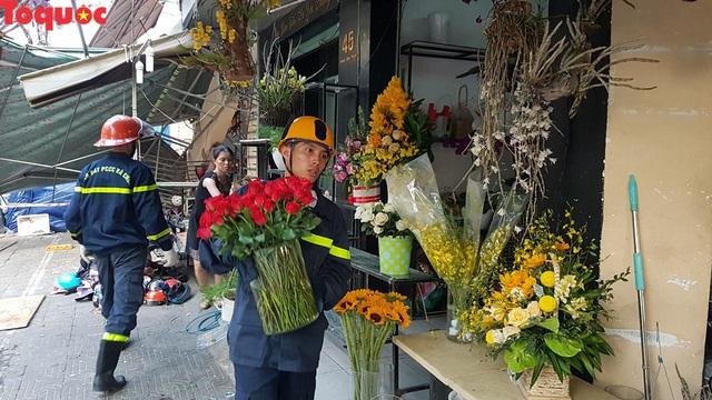 Cảnh sát giúp dân di chuyển cửa hàng hoa cạnh ngôi nhà bị sập - Ảnh 8.
