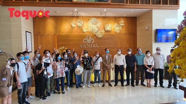 Du khách, nhân viên khách sạn và các ngành chức năng chụp ảnh làm kỷ niệm sau khi khách sạn hoàn thành cách ly.