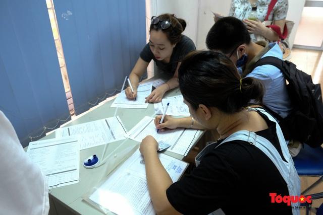 Hà Nội: Hàng trăm người xếp hàng từ sáng sớm làm thủ tục hưởng trợ cấp thất nghiệp sau Covid -19 - Ảnh 9.