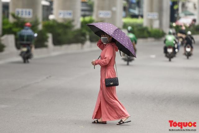 Hà Nội nắng nóng gay gắt trên 35 độ C, Người dân uể oải bịt kín mặt ra đường - Ảnh 14.