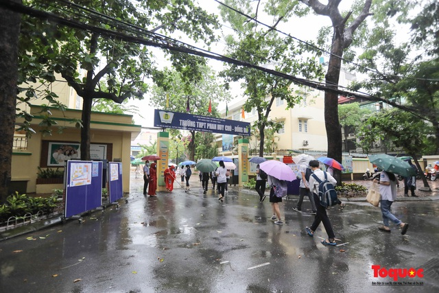 Thí sinh Hà Nội vất vả đội mưa đến trường thi vào lớp THPT - Ảnh 1.