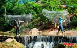 Khách du lịch thích thú trải nghiệm bắt cá suối dưới chân thác Dải Yếm