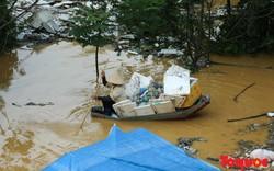Nước sông Hồng lên cao đưa rác vào nhà, người dân chèo thuyền ra vớt