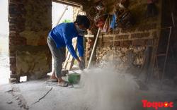 Nguời dân rắc vôi bột trắng xóa đường làng Chương Mỹ sau khi nước lũ rút